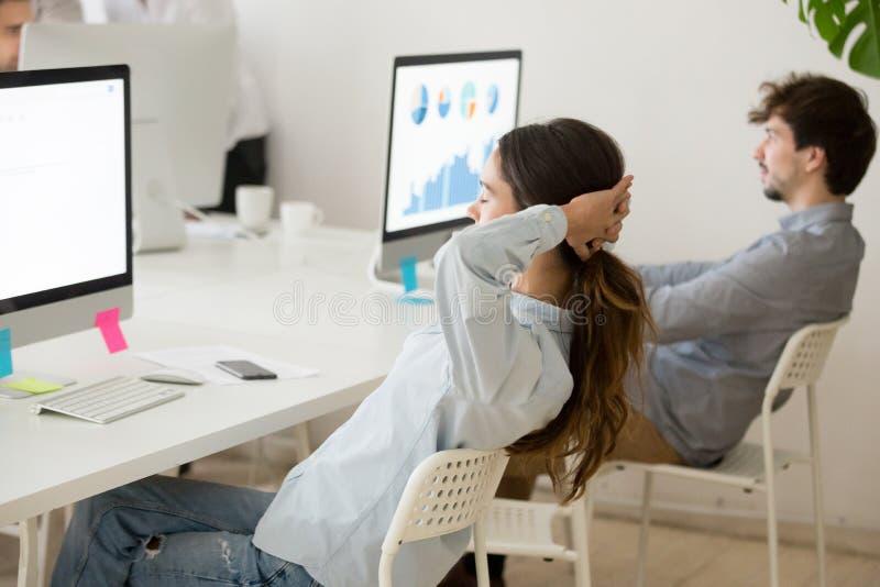 Het vrouwelijke werknemer ontspannen van de holdingshanden van het computerwerk erachter royalty-vrije stock afbeeldingen