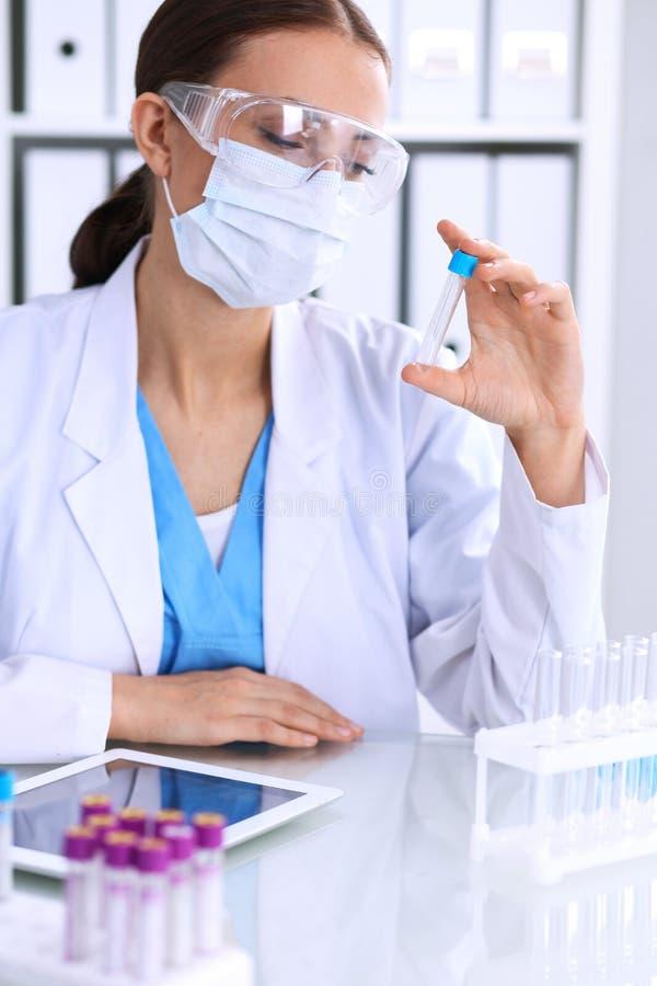 Het vrouwelijke wetenschappelijke onderzoek bekijkt de buis in laboratorium Bloedonderzoekconcept royalty-vrije stock foto