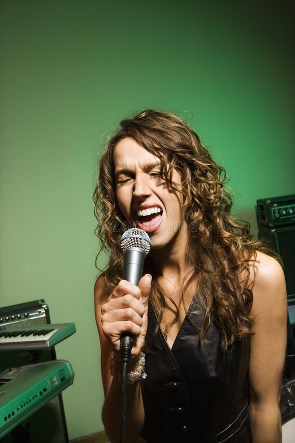 Het vrouwelijke zingen in mic. stock foto's