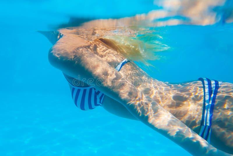 Het vrouwenlichaam zwemt onderwater in het zwembad royalty-vrije stock foto