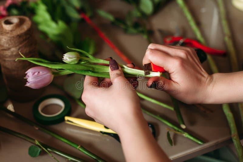 Het vrouwenwerk boven lijst met bloemisthulpmiddelen stock foto