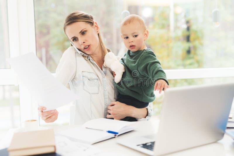 Het vrouwenwerk tijdens zwangerschapsverloven thuis Een vrouw werkt en zorgen tegelijkertijd voor een kind royalty-vrije stock afbeelding