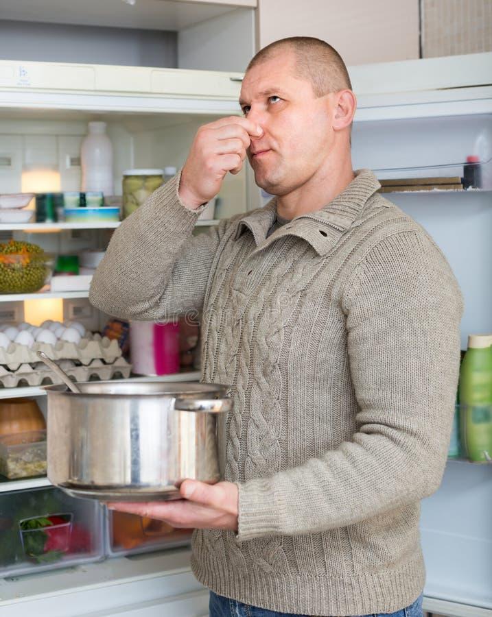Het vuile voedsel van de mensenholding dichtbij koelkast stock foto's