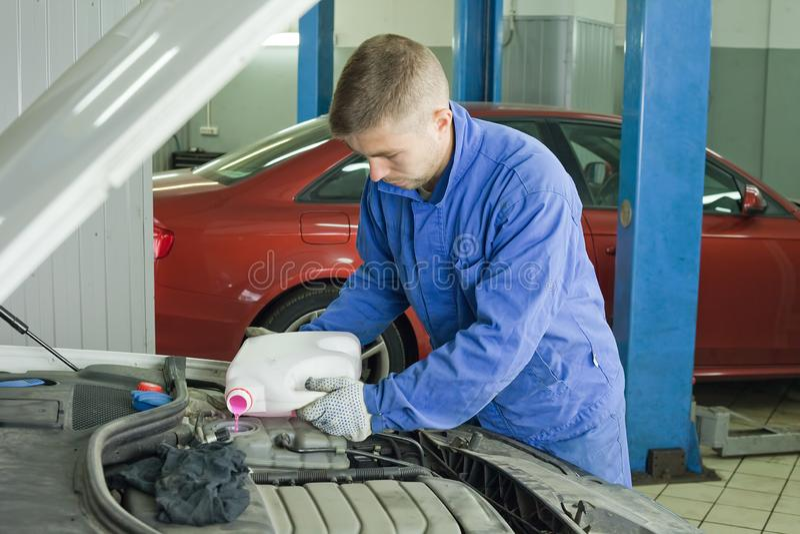 Het vullen van de auto met antivriesmiddel De meester in de workshop opent de tank en giet roze koelmiddel stock afbeeldingen