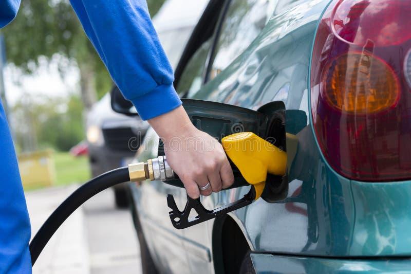 Het vullen van de mens benzinebrandstof in de pijp van de autoholding stock afbeeldingen