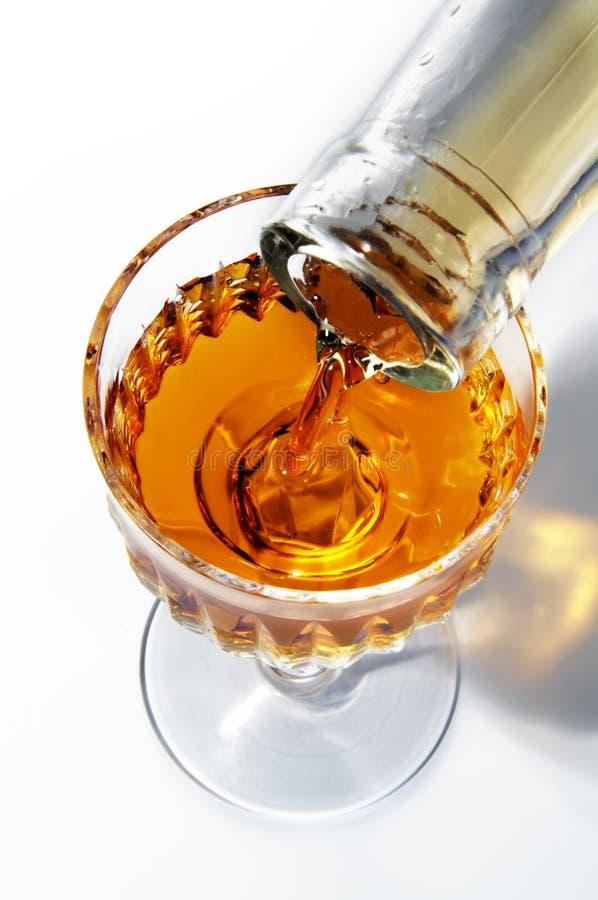 Het vullen van een wijnglas door een alcohol stock foto