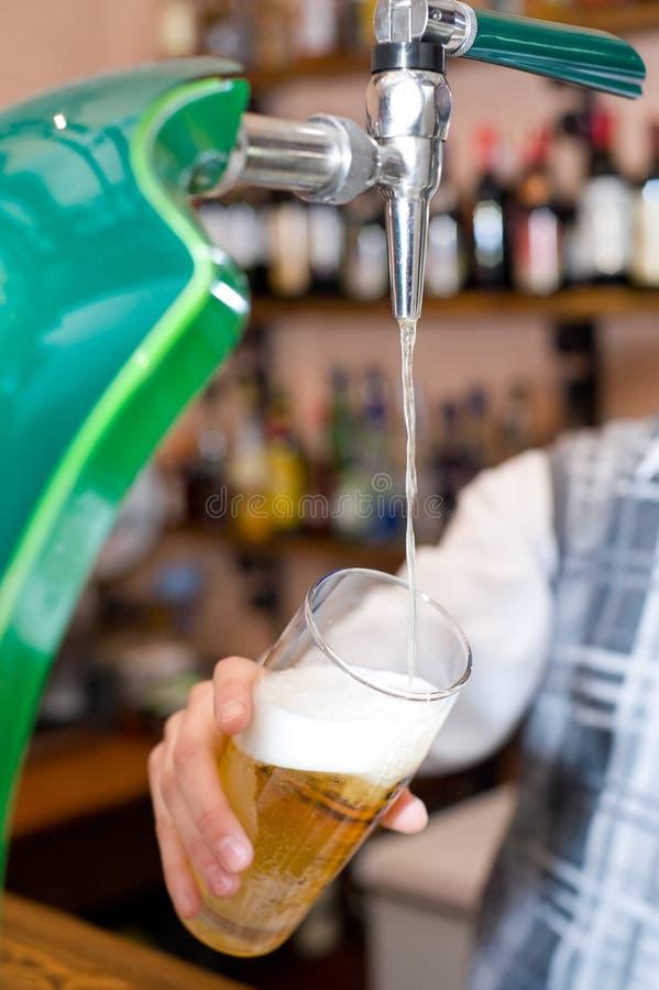 Het vullen van glas met bier van tapkraan stock foto's