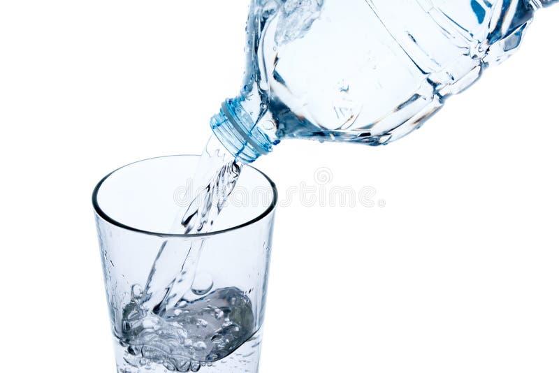 Het vullen van glas met water van plastic fles stock foto's