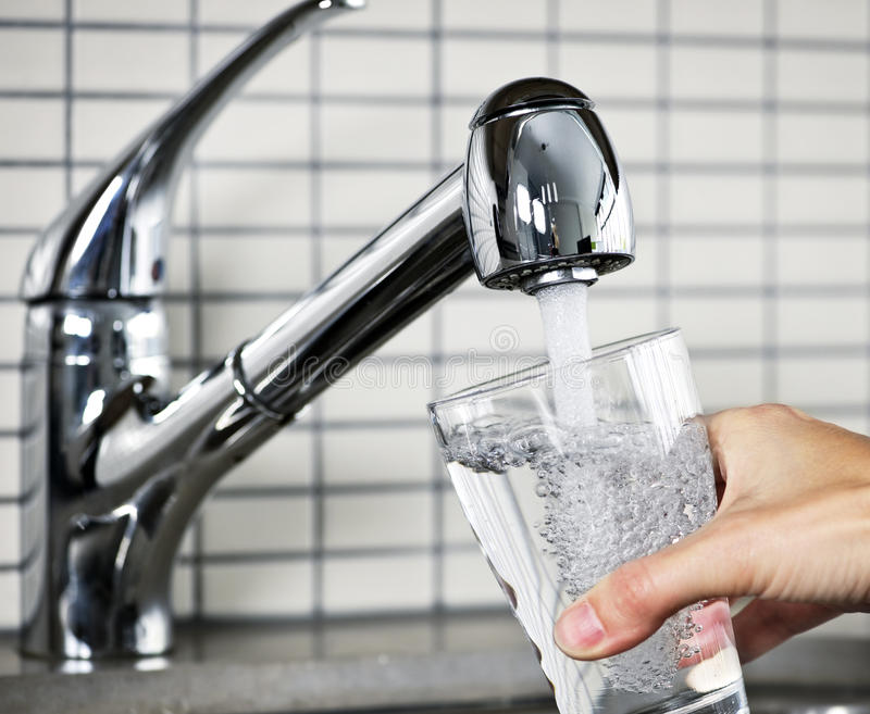 Het vullen van glas van leidingwater stock fotografie