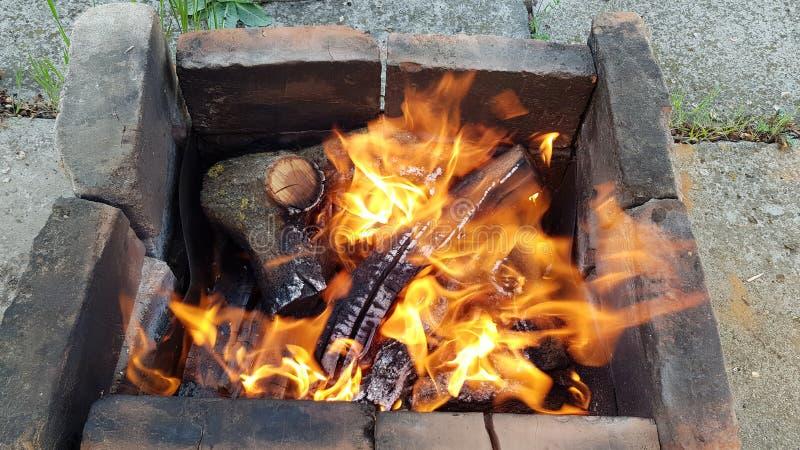 Het vuur met heldere oranje vlam in oude brandhoutkoperslager maakte van gebrande rokerige bakstenen in grond stock afbeelding