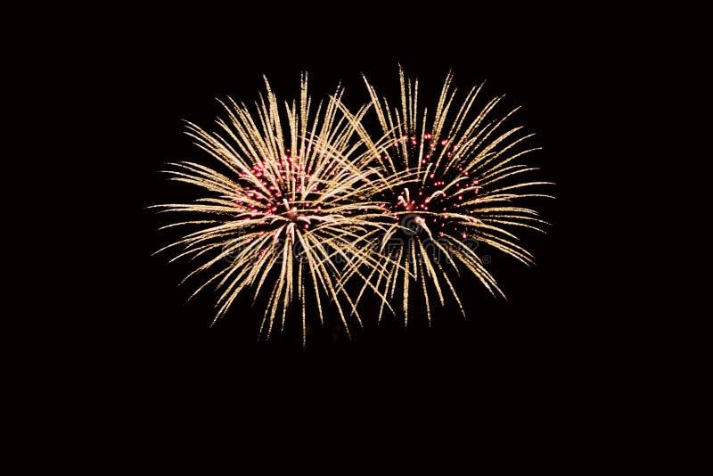 Het vuurwerk van de nieuwjarenvooravond, twee tacets die als twee prachtige boeketten van bloemen in geeloranje rood licht voor a stock foto's