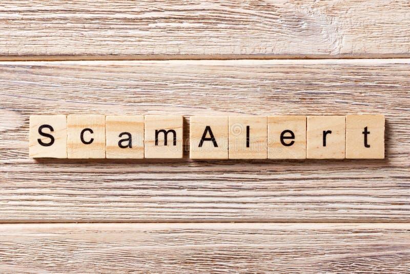 Het waakzame die woord van Scam op houtsnede wordt geschreven De waakzame tekst van Scam op lijst, concept royalty-vrije stock foto