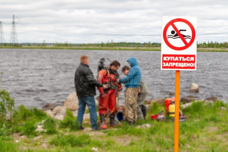 Het waarschuwingsbord op de kust met inschrijving-u kan niet duiken Op de achtergrond, duikers, voorbereidingen voor het werk royalty-vrije stock afbeeldingen