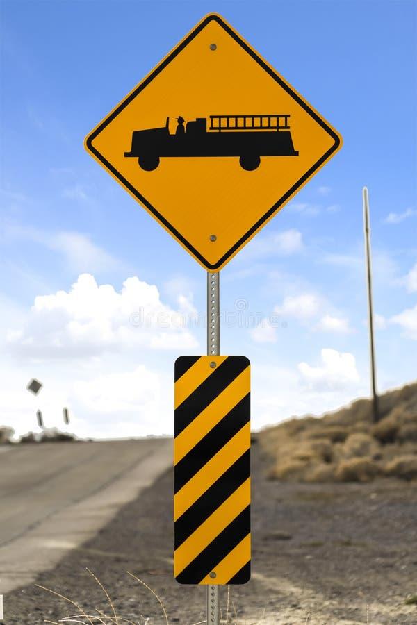 Het Waarschuwingsbord van de brandweerkazernevooruitgang naast een weg met bewolkte blauwe hemelachtergrond royalty-vrije stock fotografie