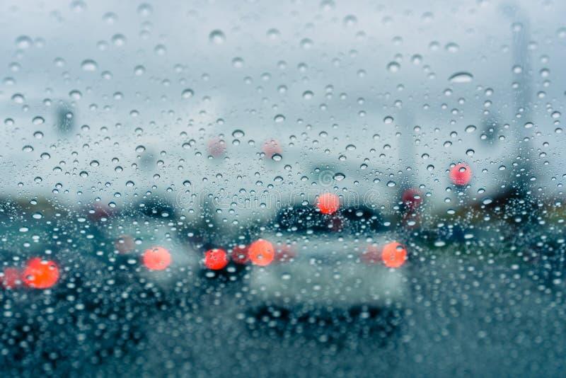 Het wachten bij een verkeersverbinding op het groene licht tijdens een regenachtige dag; stock fotografie