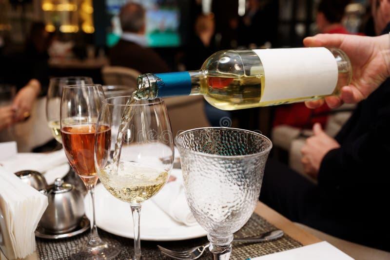 Het wachten giet witte wijn stock foto