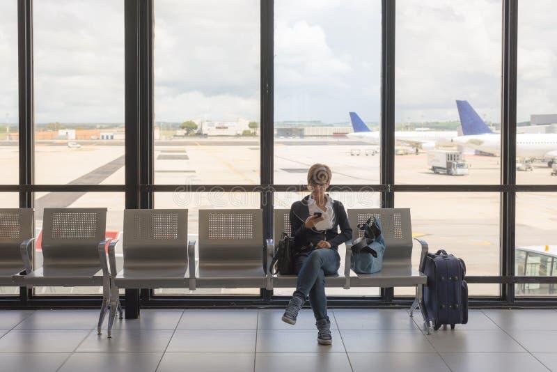 Het wachten in luchthaven eind gebruikende telefoon stock afbeeldingen