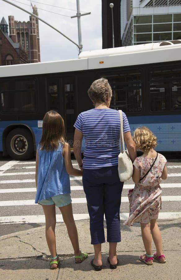 Het wachten om een bezige straatvrouw met twee kinderen te kruisen royalty-vrije stock foto's