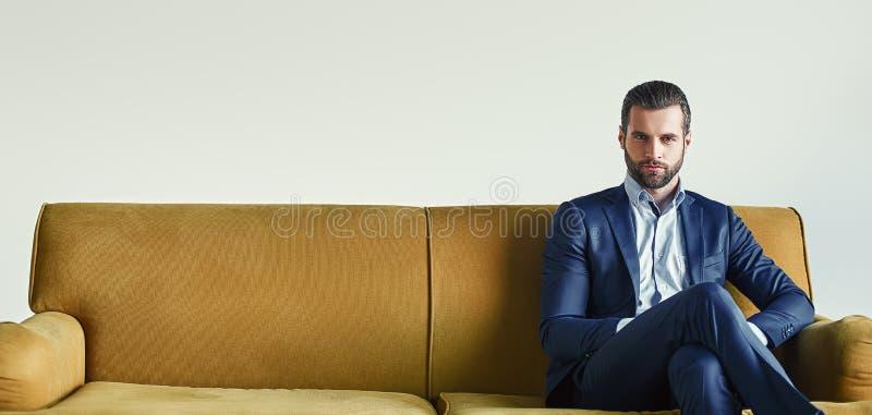 Het wachten op een vergadering De goed-geklede jonge en succesvolle zakenman zit op bank op kantoor en wacht somebody royalty-vrije stock foto
