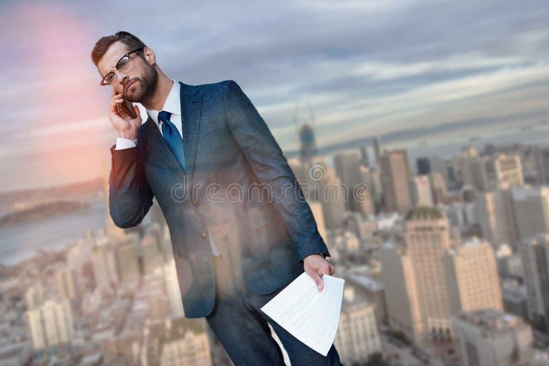 Het wachten op een vergadering Ernstige en succesvolle zakenman die telefonisch spreken en documenten houden terwijl status tegen royalty-vrije stock foto