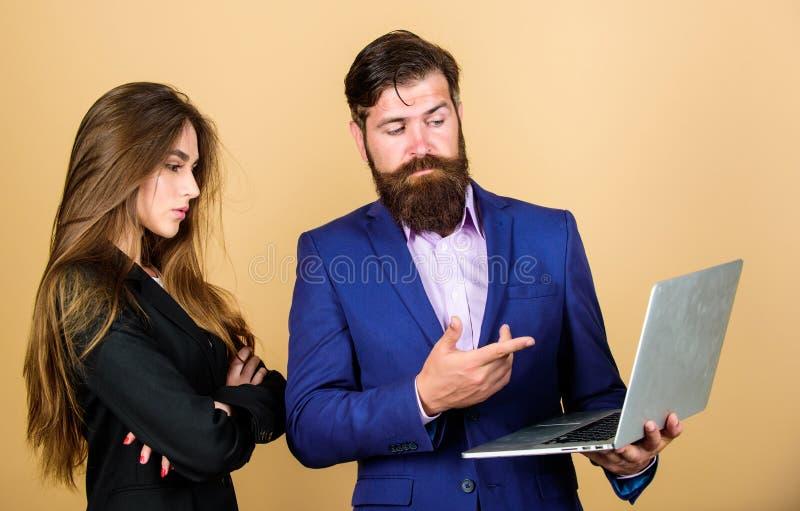 Het wachten op nieuwe idee?n Bedrijfs paar zekere rijpe mens met laptop sexy vrouwensecretaresse die in computer kijkt royalty-vrije stock afbeeldingen