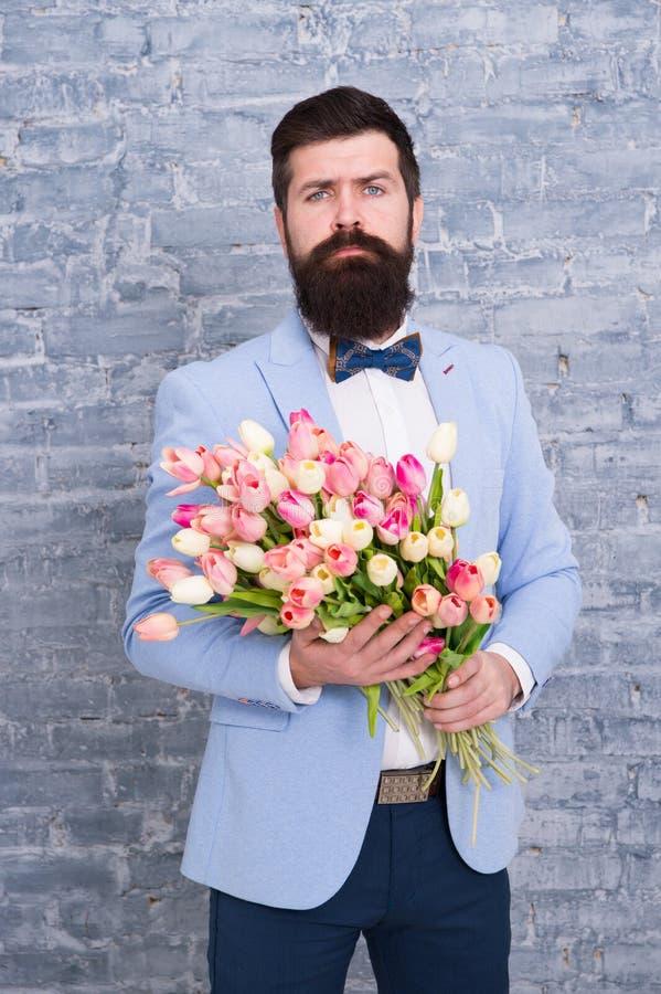 Het wachten op zijn meisje Romantische mens met bloemen Romantische gift Macho die klaar romantische datum krijgen Tulpen voor royalty-vrije stock afbeelding