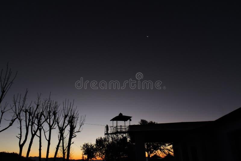Het wachten op zonsopgang onder halve maan stock afbeeldingen