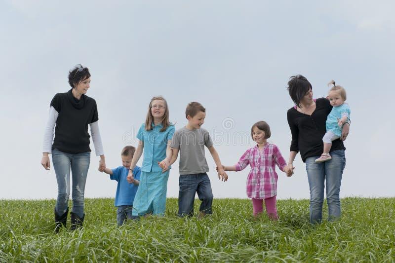 Het walkiing van de familie in de weide stock afbeelding