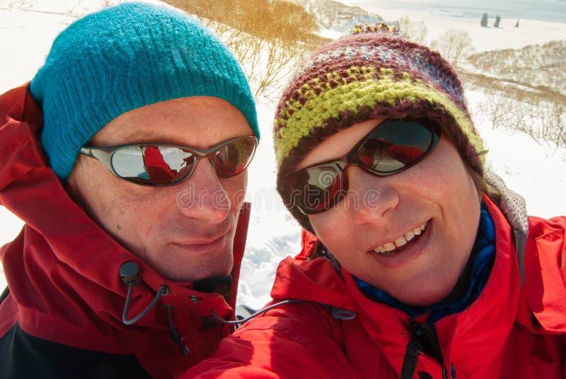 Het wandelaarpaar heeft pret in de de winterbergen stock afbeelding