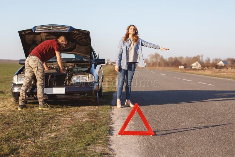 Het wanhopige wijfje houdt voertuigen op weg tegen aangezien de behoeften helpen, samen met echtgenoot door auto reizen en schade royalty-vrije stock fotografie
