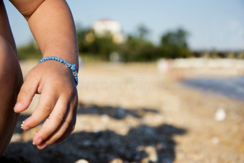 Het wapen van het jonge geitje met armband op zandig strand royalty-vrije stock fotografie