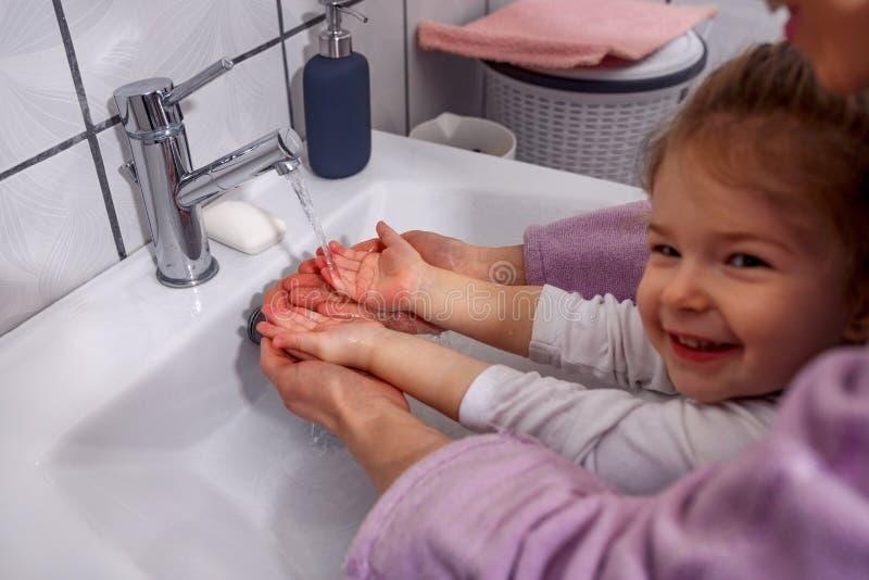 Het wassen van handen is de grappige moeder en het glimlachen jong geitjehanden w van de meisjeswas stock fotografie