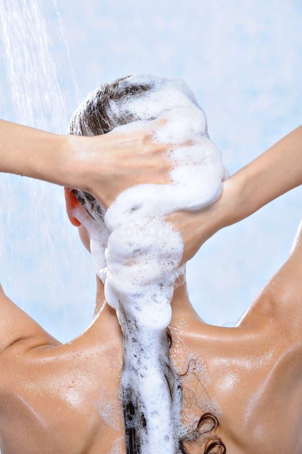 Het wassen van lang donkerbruin vrouwelijk haar door shampoo royalty-vrije stock fotografie