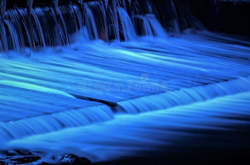 Het water is de bron van het leven/Waterwervelingen bij een show in blauw licht worden verpakt dat stock afbeelding