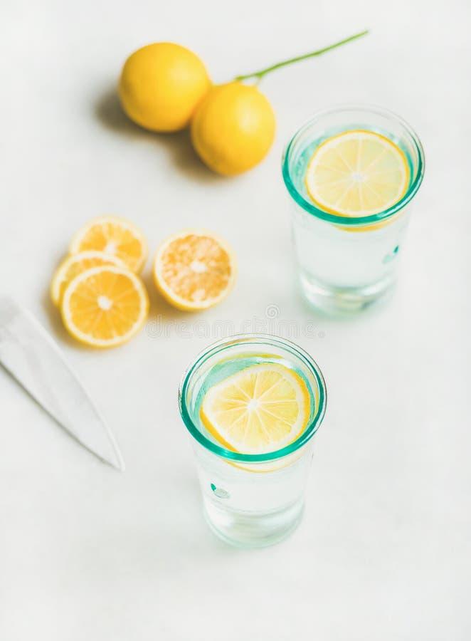 Het water van de Detoxcitroen in glazen met verse citroenvruchten die worden gediend royalty-vrije stock afbeeldingen