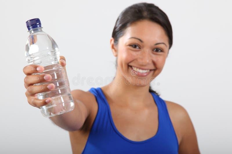 Het water van de fles dat door mooie glimlachende jonge vrouw wordt gehouden stock fotografie