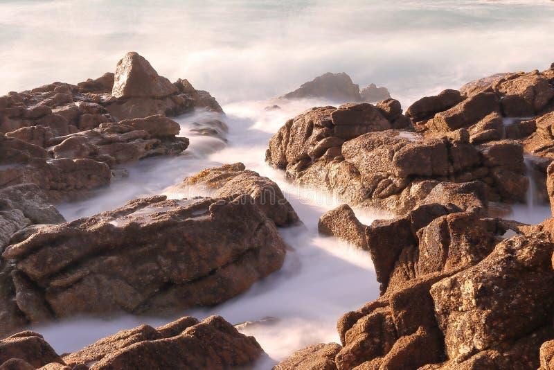 HET WATER VAN DE GOLVEN VAN HET OVERZEES DIE SOMMIGE KLIPPEN REIZEN BIJ ZONSONDERGANG stock afbeeldingen