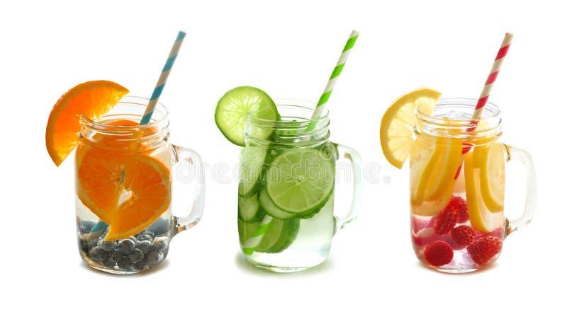 Het water van het Detoxfruit in metselaarkruiken met geïsoleerd stro stock afbeelding