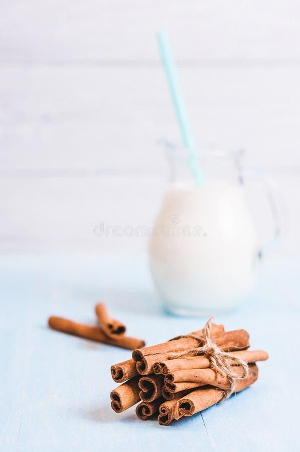 Het waterkruikglas melk met kaneel en cocktailbuis op blauwe houten achtergrond instagram filtreert stock afbeelding