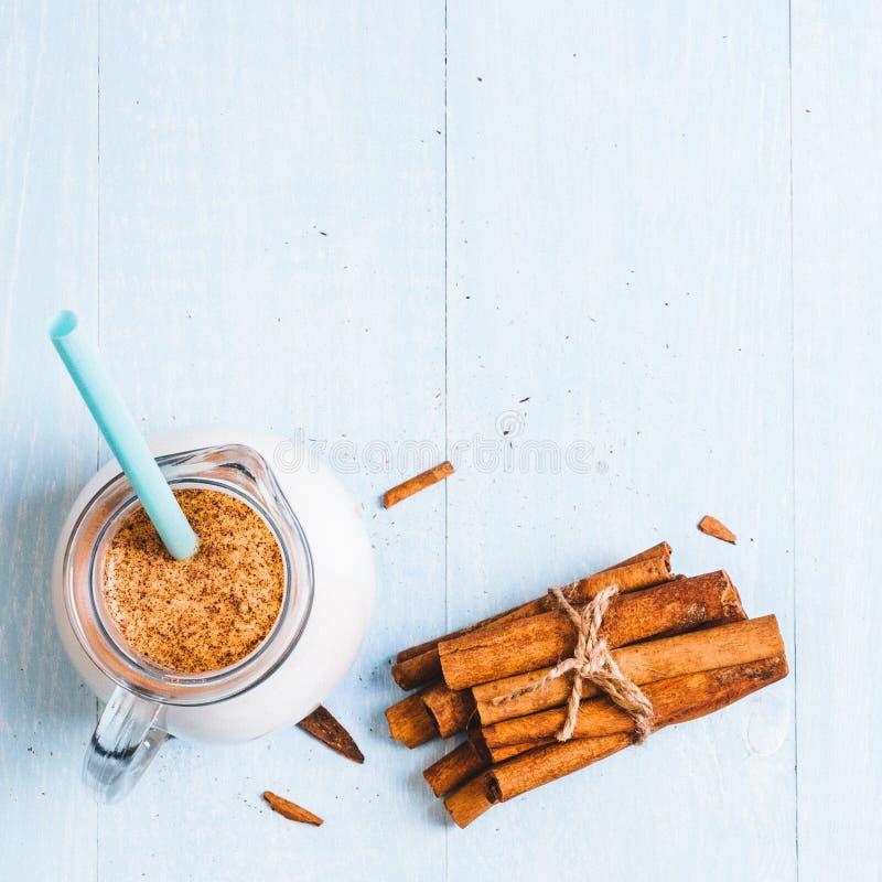 Het waterkruikglas melk met kaneel op een blauwe houten achtergrond, instagram filtreert ruimte voor tekst stock afbeelding