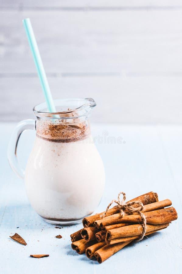 Het waterkruikglas melk met kaneel op een blauwe houten achtergrond, instagram filtreert ruimte voor tekst stock fotografie