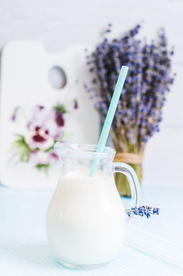 Het waterkruikglas melk met lavendel en cocktailbuis op een blauwe houten achtergrond instagram filtreert stock foto