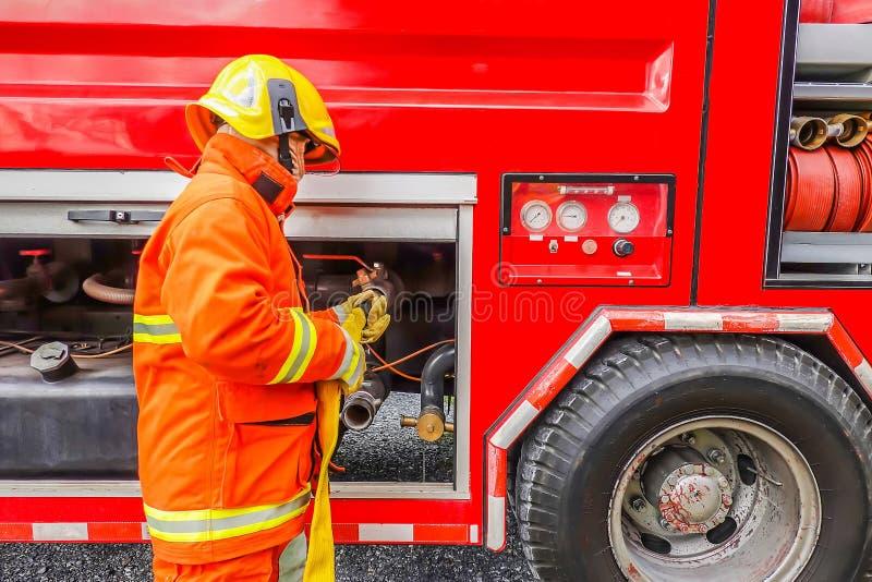 Het waterslang van de brandbestrijdersholding dichtbij de vrachtwagen met materiaal stock foto