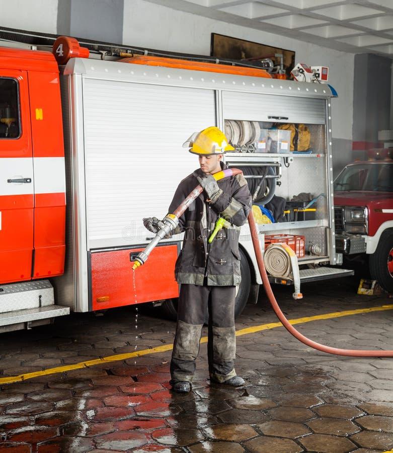 Het Waterslang van de brandweermanholding tijdens Opleiding stock foto's