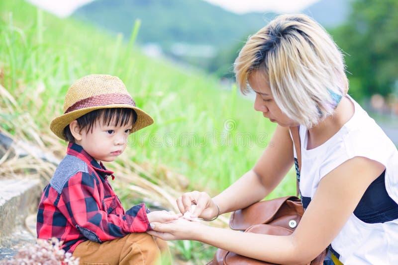 Het weefsel van het mammagebruik om kind schoon te maken dient het park in Een hoed van de kindslijtage royalty-vrije stock afbeelding