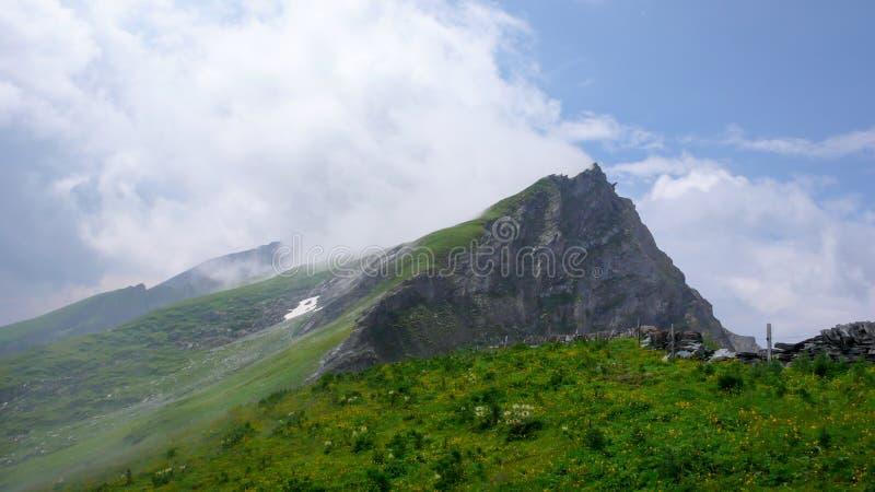 Het weelderige groene berglandschap en de bergpiek met lichte witte wolken en een scherpe klip lopen terug royalty-vrije stock foto's