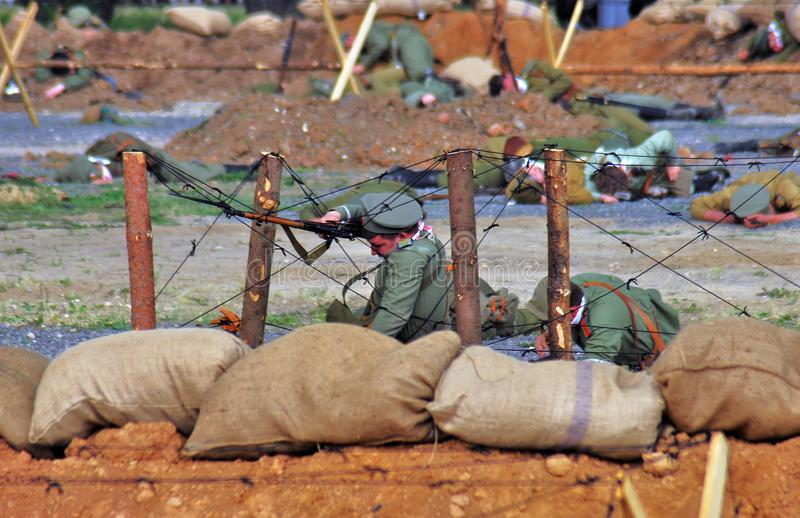Het weer invoeren van de Osovetsslag Reenactor legt op de grond die een kanon houden stock afbeelding