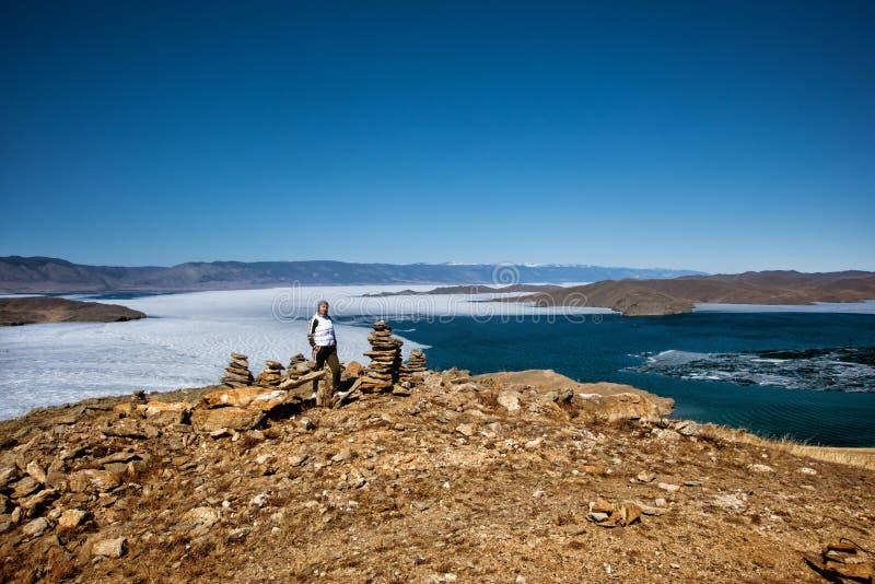 Het Weergeven boven groot mooi meer Baikal met Ijsijsschollen die op het water en het meisje drijven bevindt zich dichtbij rotsen stock afbeelding