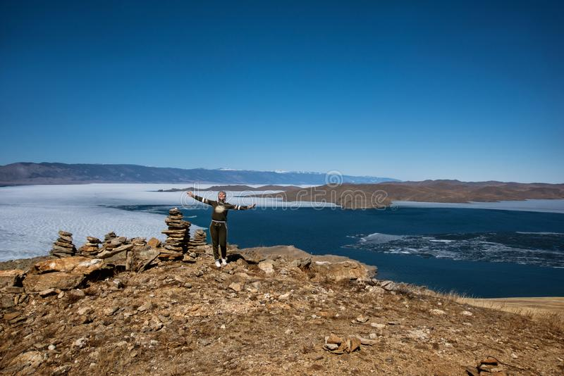 Het Weergeven boven groot mooi meer Baikal met Ijsijsschollen die op het water en het meisje drijven bevindt zich dichtbij rotsen stock foto's