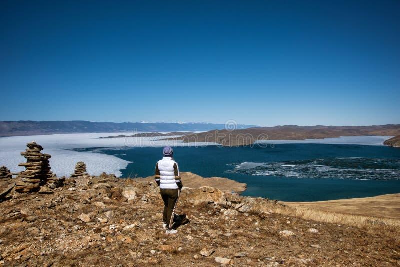 Het Weergeven boven groot mooi meer Baikal met Ijsijsschollen die op het water en het meisje drijven bevindt zich dichtbij rotsen royalty-vrije stock fotografie